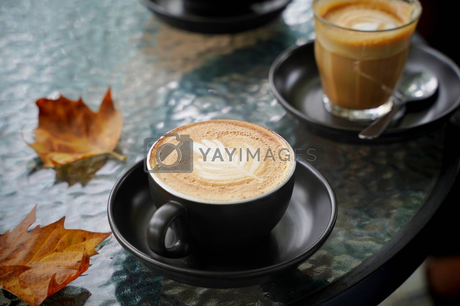 Royalty free image of Hot cup of coffee latte and flat white with autumn leaves on the by nuchylee