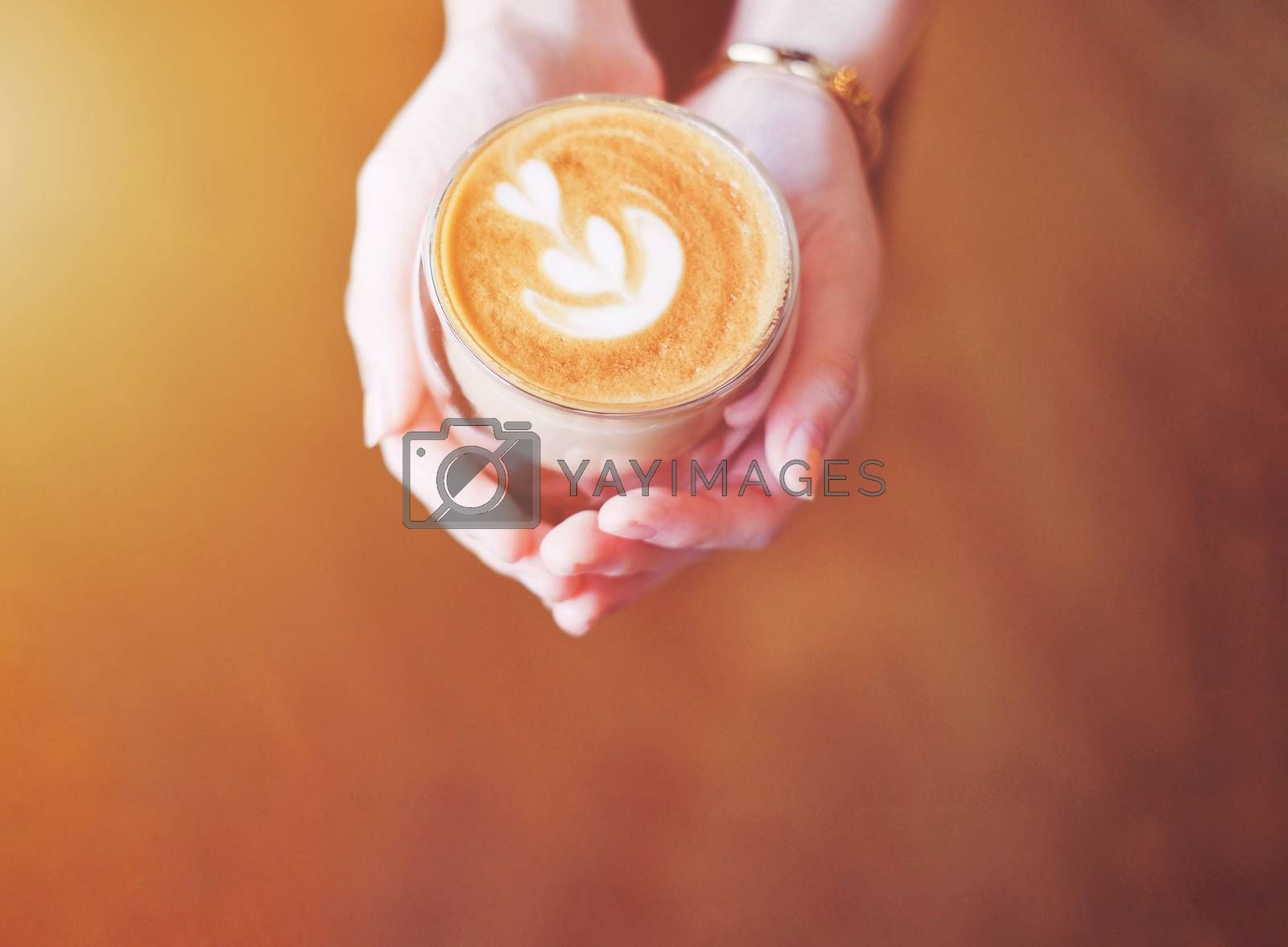 Royalty free image of Close up hands of barista woman holding cup of hot cappuccino co by nuchylee