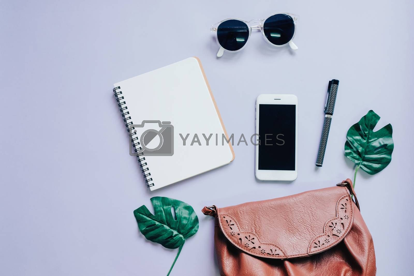 Royalty free image of Top view flat lay of woman bag with smartphone, blank notebook,  by nuchylee