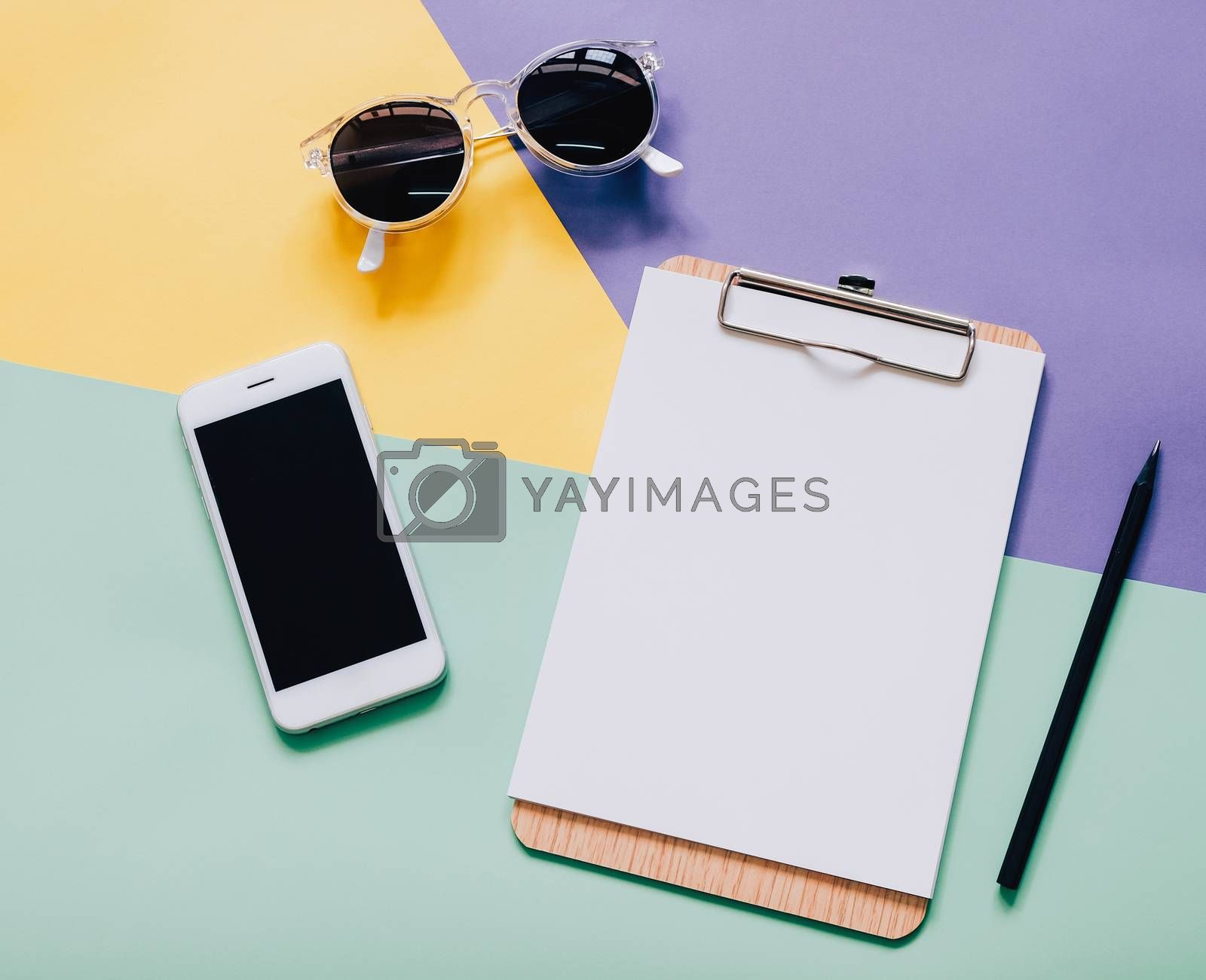 Creative flat lay style workspace desk with smartphone, blank clipboard and sunglasses on modern colorful background