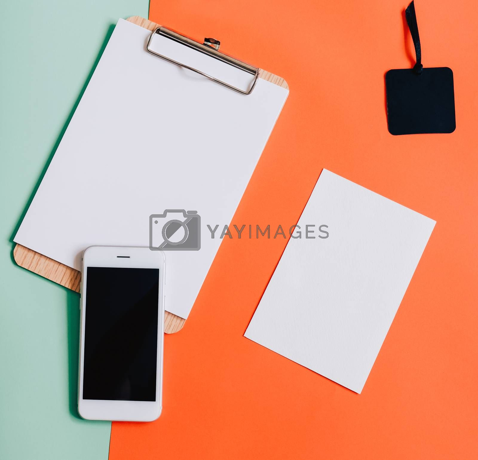 Royalty free image of Creative flat lay of smartphone, blank clipboard and white card  by nuchylee