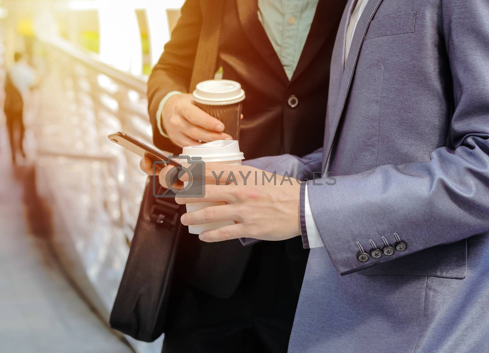 Royalty free image of Midsection of two colleague businessmen using smartphone and dri by nuchylee