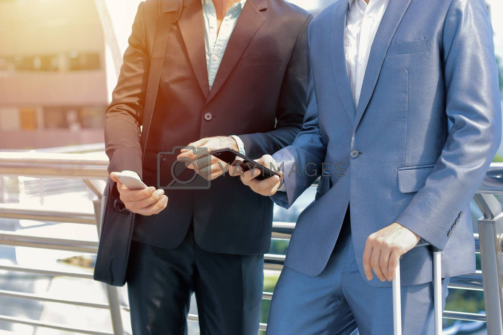 Royalty free image of Midsection of two colleague businessmen using smartphone at the  by nuchylee