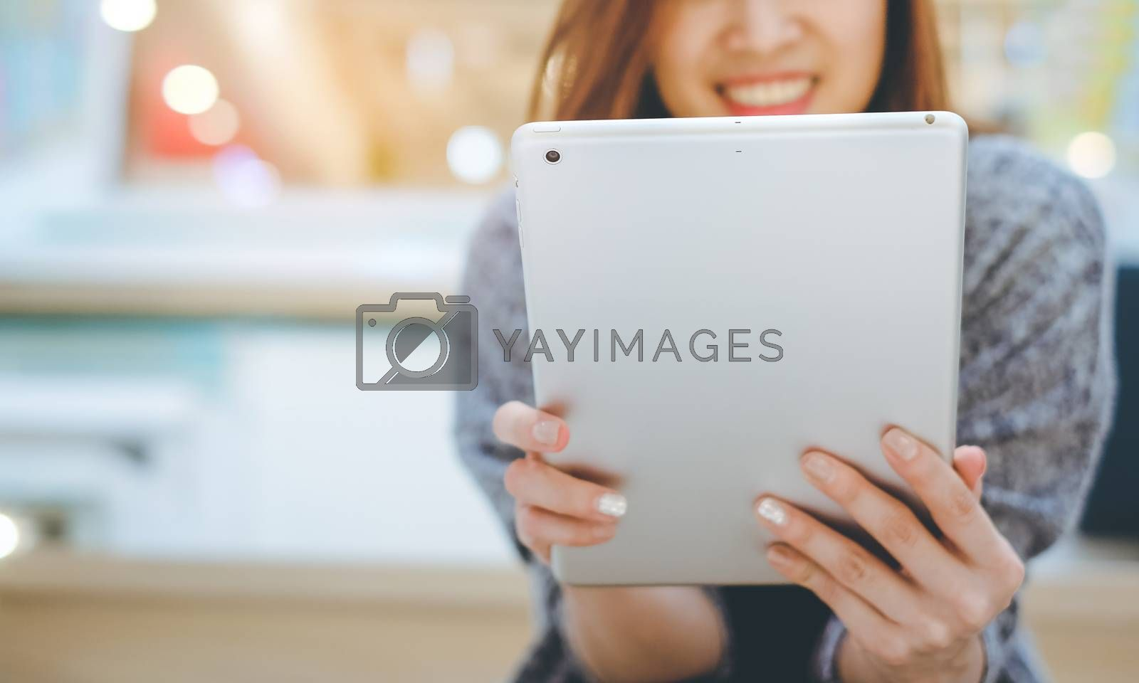 Royalty free image of Young asian woman smiling and using tablet in modern office or s by nuchylee