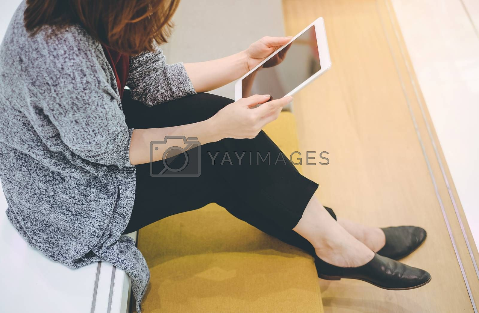Royalty free image of Young asian woman enjoy using tablet in modern office or shoppin by nuchylee