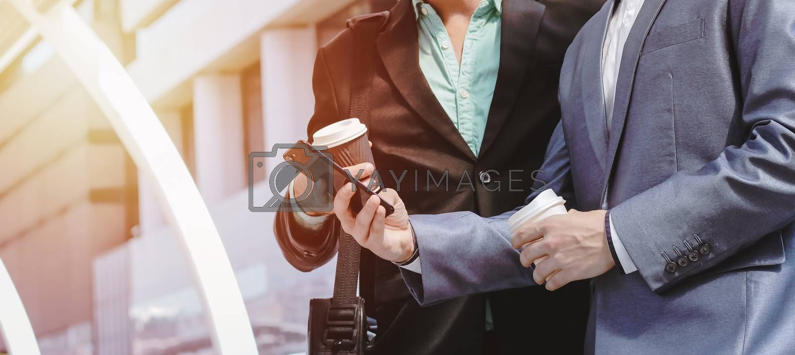 Royalty free image of Midsection of two colleague businessmen using smartphone and hol by nuchylee