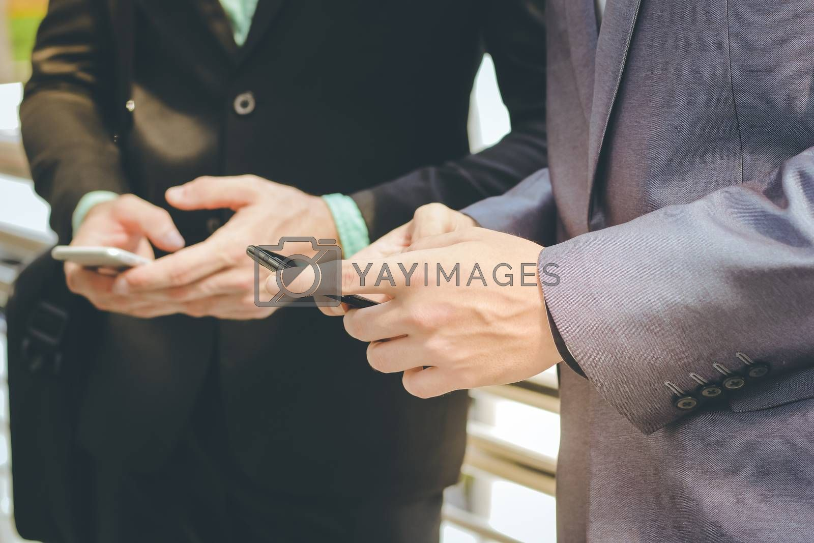 Midsection of two colleague businessmen using smartphone, business and technology concept