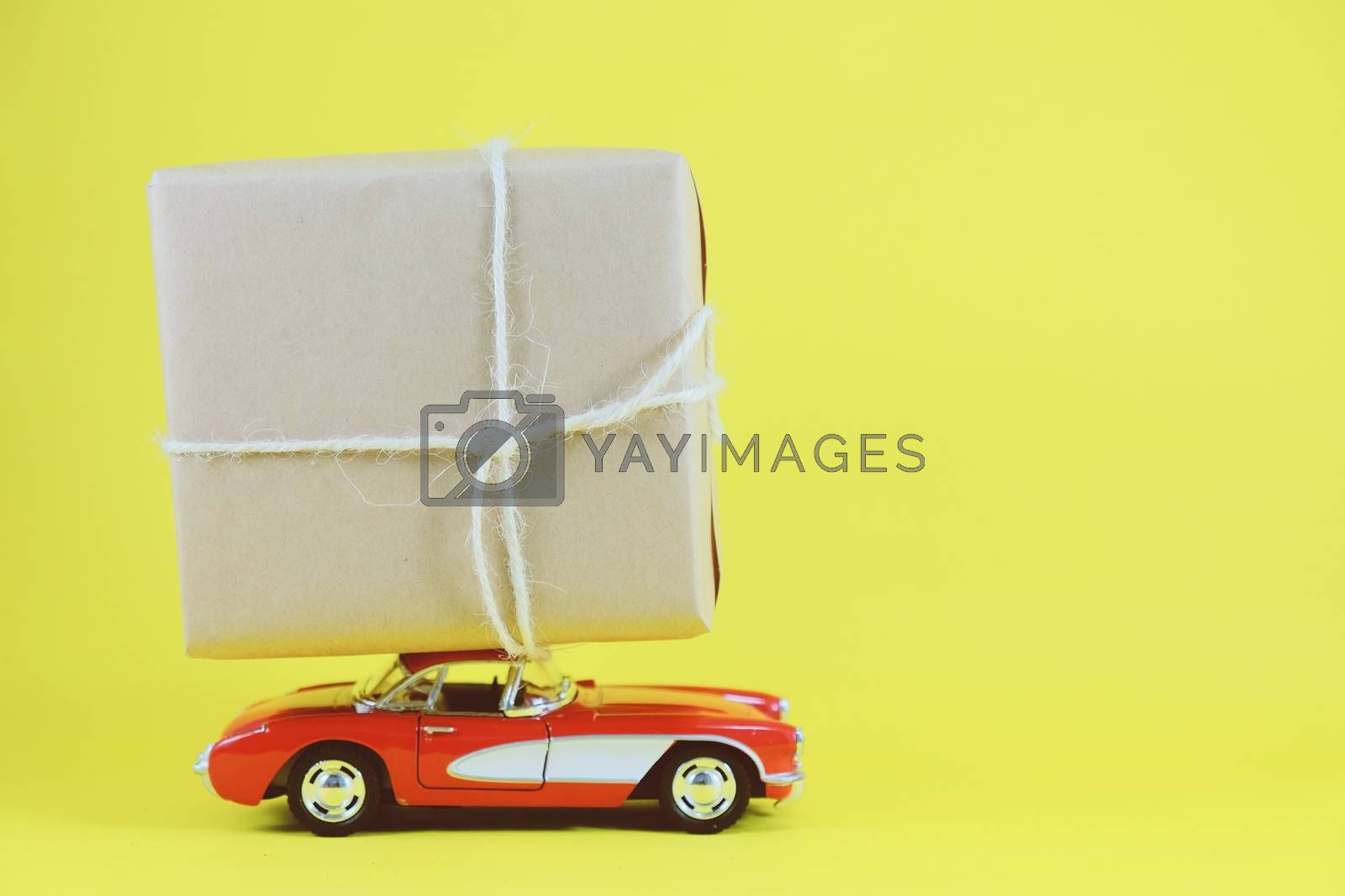 Red retro toy car delivering gift box for holiday season on yellow background with copy space