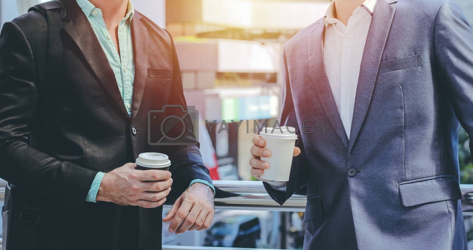 Midsection of two colleague businessmen using smartphone and holding coffee cup at the outside of modern office building with copy space and sunlight tone
