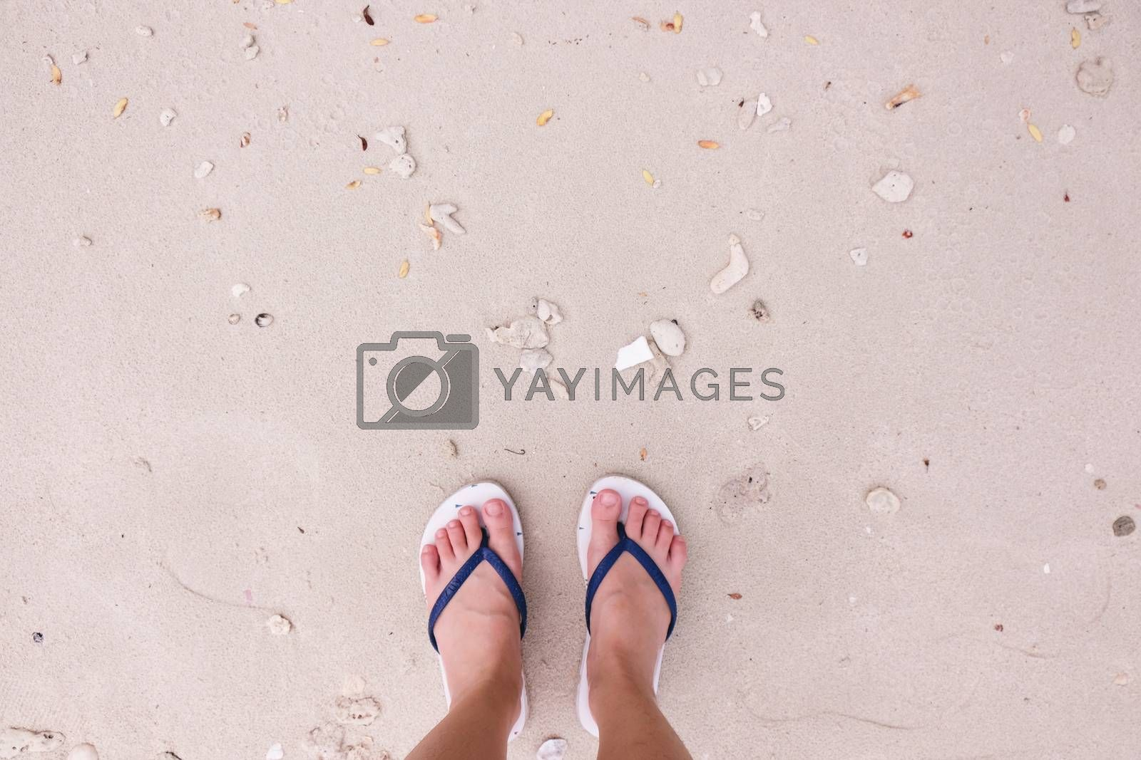 Selfie of feet in fashion sandals on sand beach background, top view with copy space