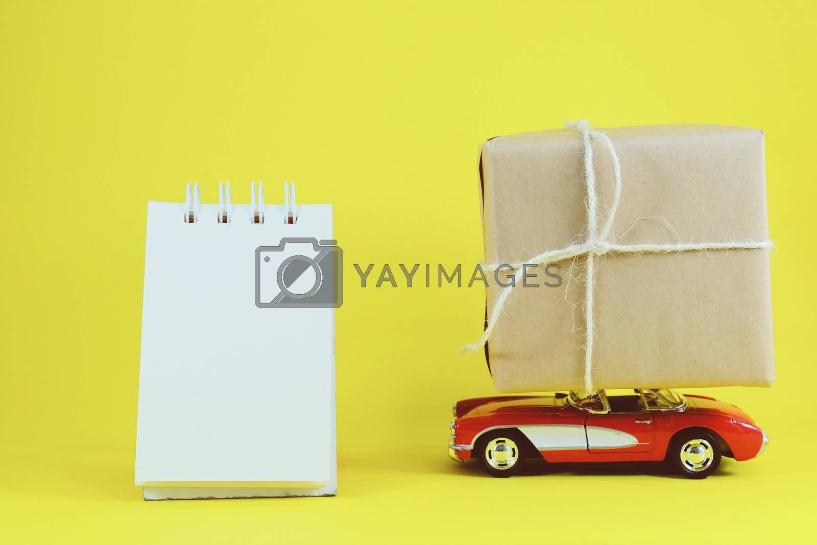 Red retro toy car delivering gift box for holiday season on yellow background with blank notebook
