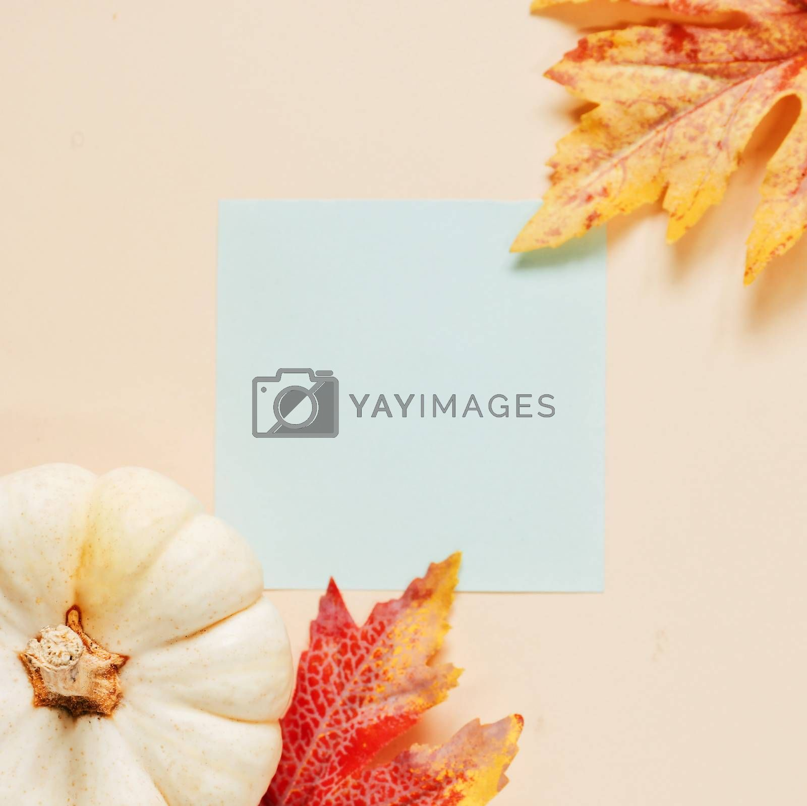 Flat lay of minimal workspace blank notebook with autumn leaves and pumpkin on yellow background, autumn and thanksgiving concept
