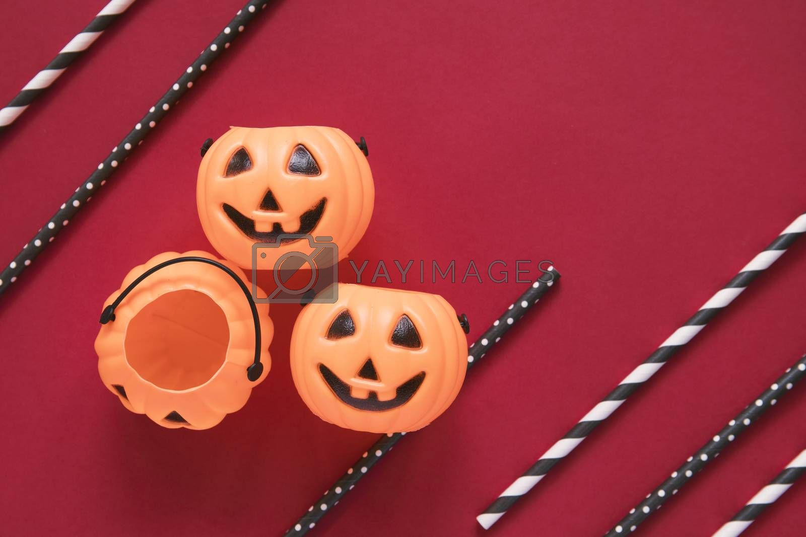 Flat lay style of halloween party concept with decorative pumpkins and black fancy straw on red background, copy space
