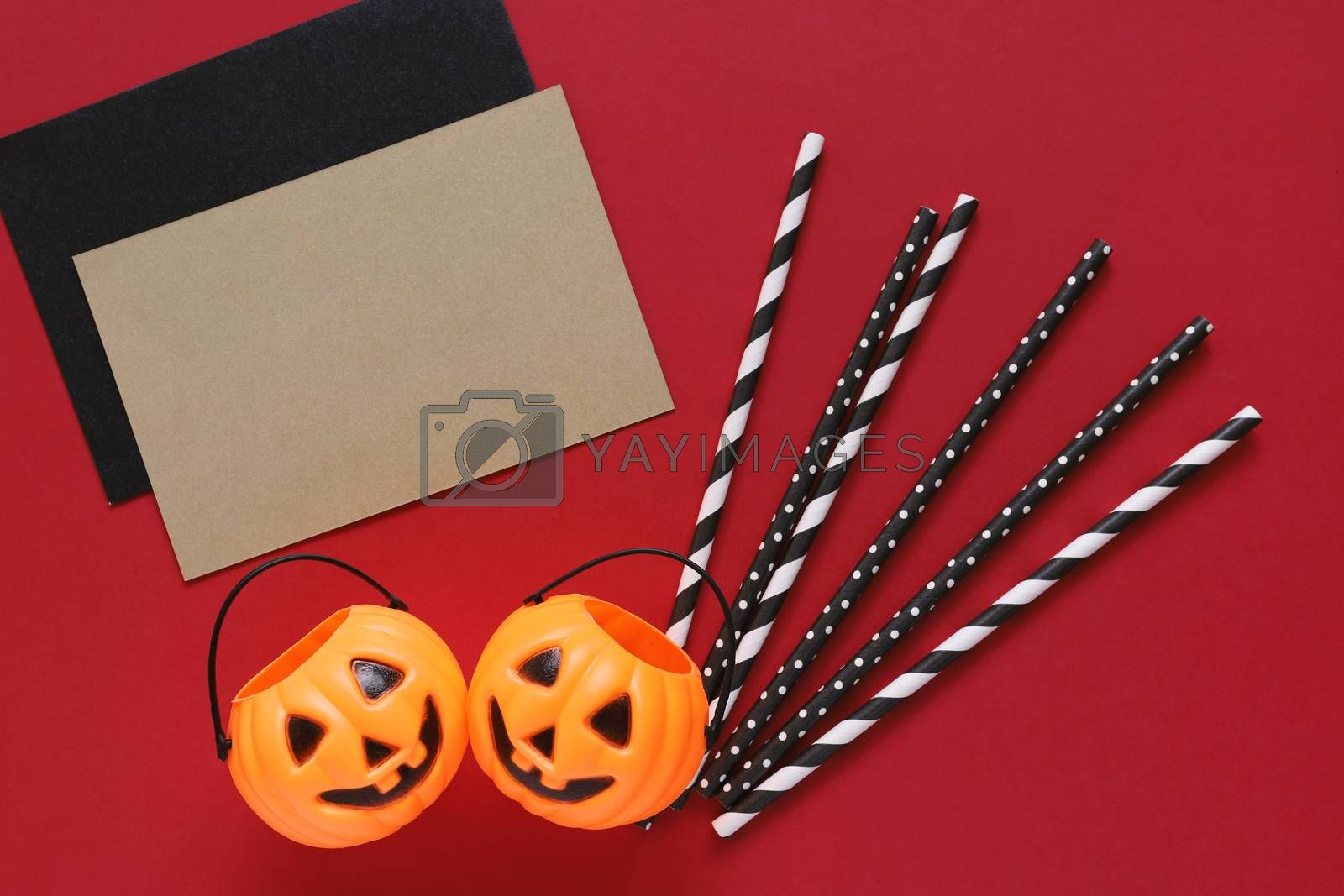Flat lay style of halloween party concept with decorative pumpkins and black fancy straw with blank card on red background