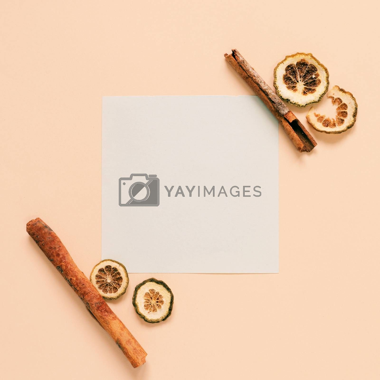 Flat lay of blank paper with cinnamon sticks and herb on yellow background, autumn and thanksgiving concept, minimal style