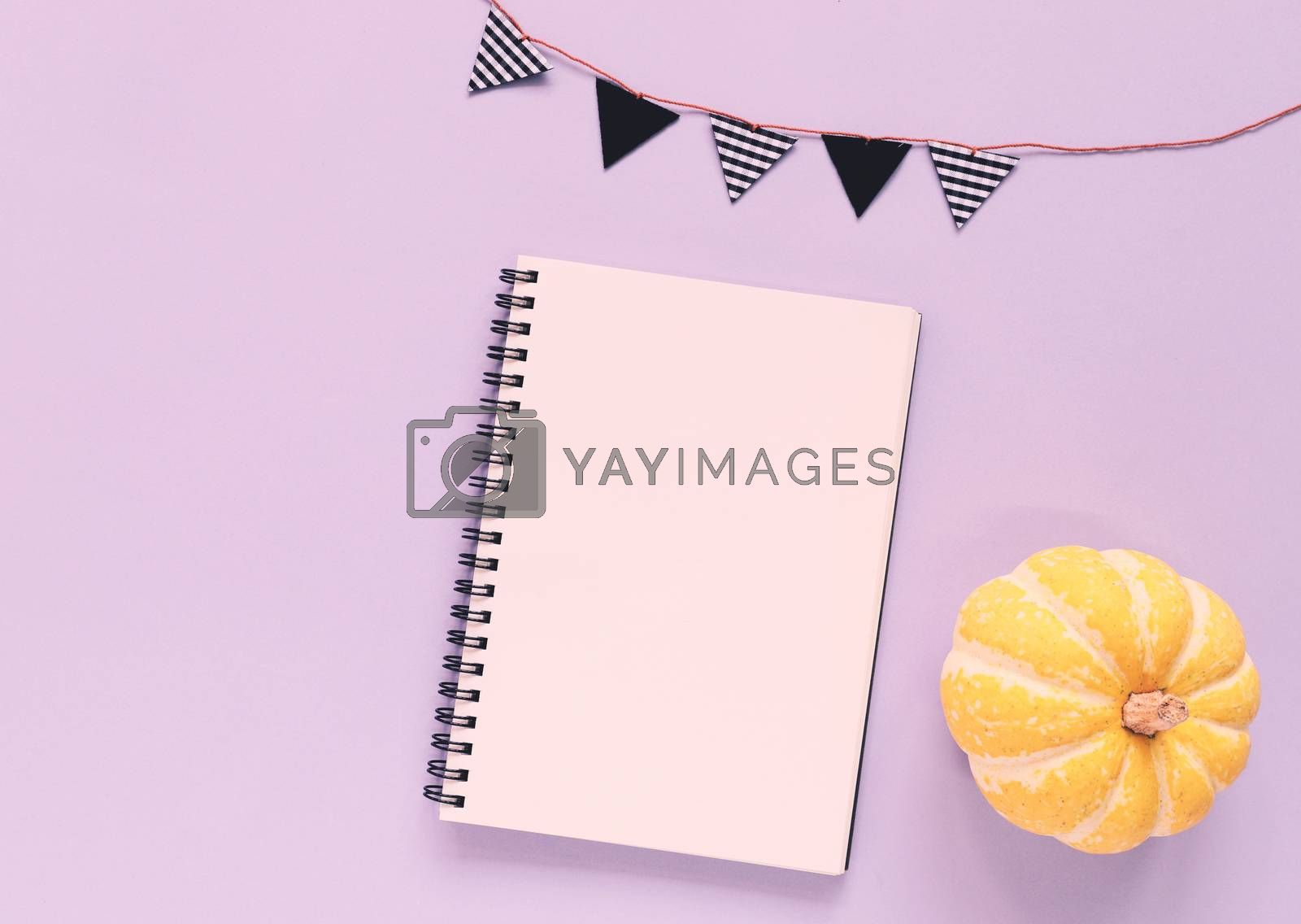 Flat lay of minimal workspace blank notebook with pumpkin and bunting flag on purple background, copy space