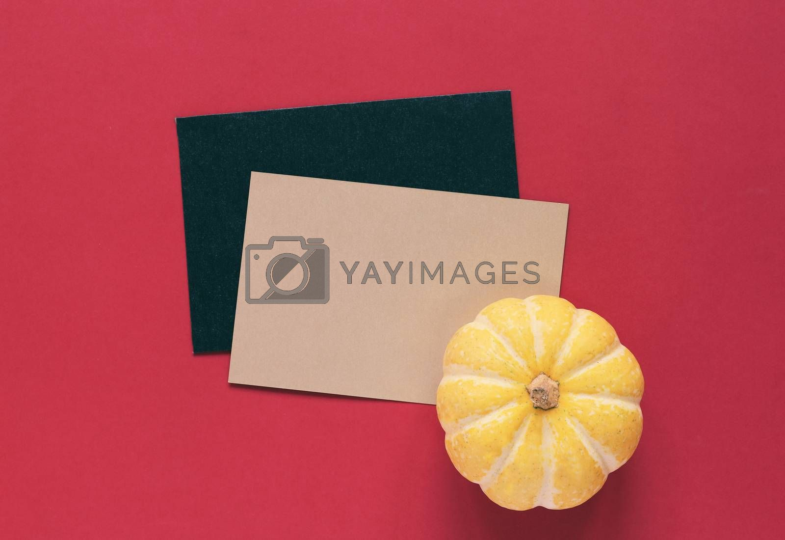 Yellow pumpkin on blank greeting card with red background, halloween or thanksgiving concept