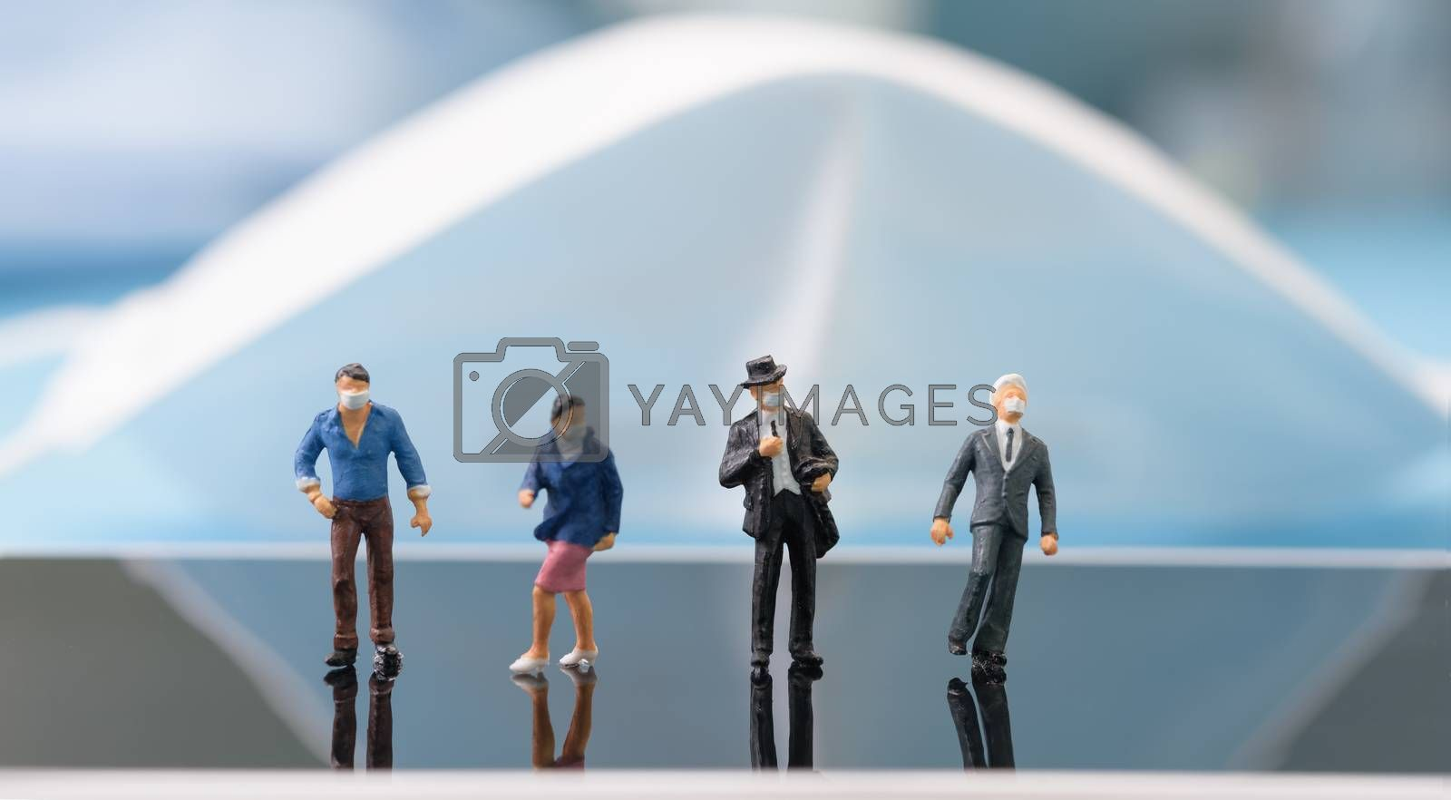 Miniture business people wear mask stand on mobile phone over blue background,due to  Pandemic coronavirus(COVID-19) conceptual.