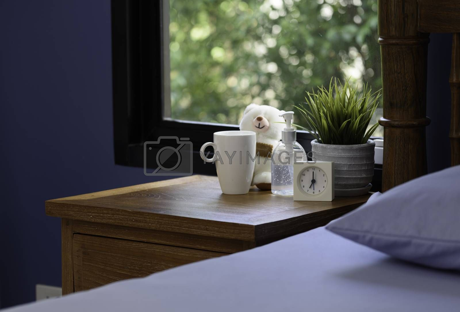 Hand sanitizer,white cup,teddy bear and alarm clock on wood table in blue bedroom while Covid-19  home quarantine .