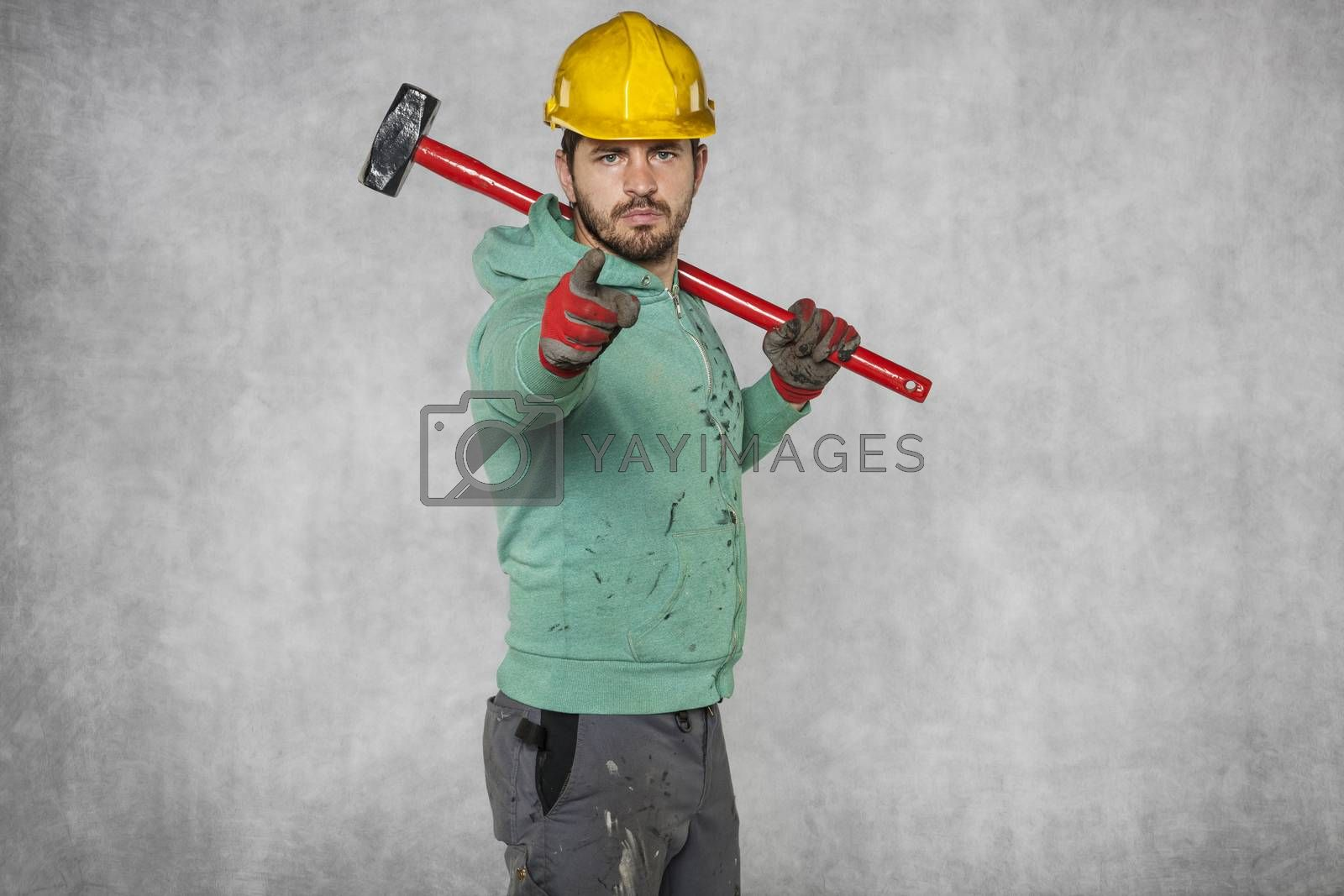 a worker with a big hammer on his shoulder, points to you