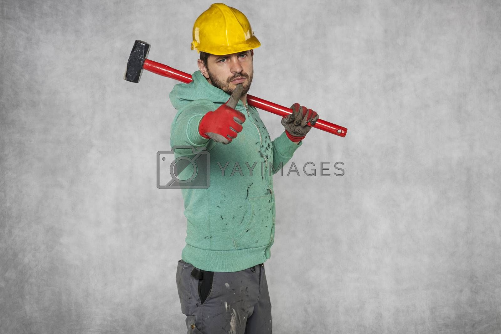 worker with a big hammer on his shoulder, thumb up