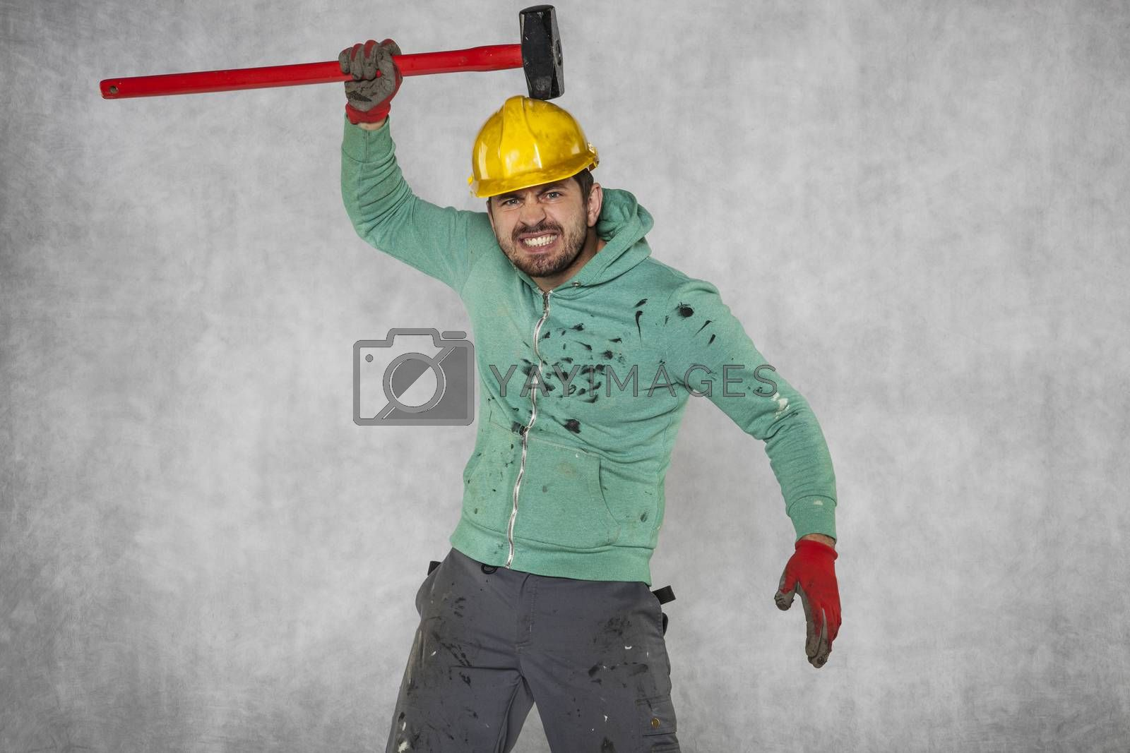 A mad worker hits himself witch a big hammer
