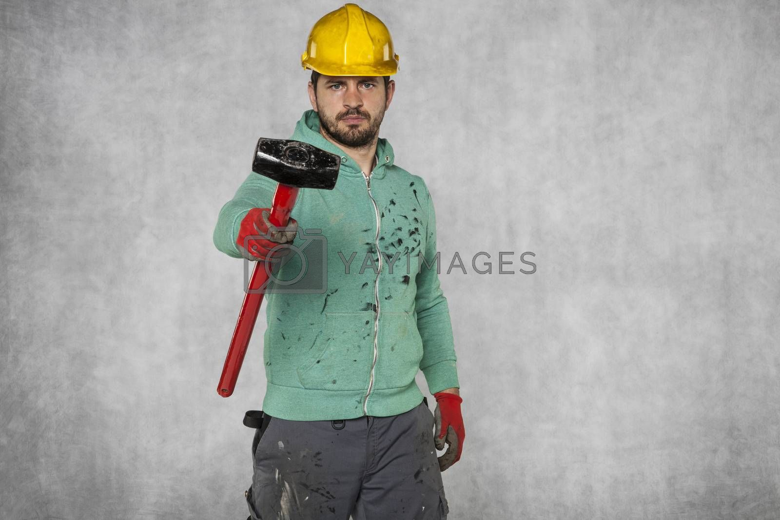A worker with a big hammer looks at the camera
