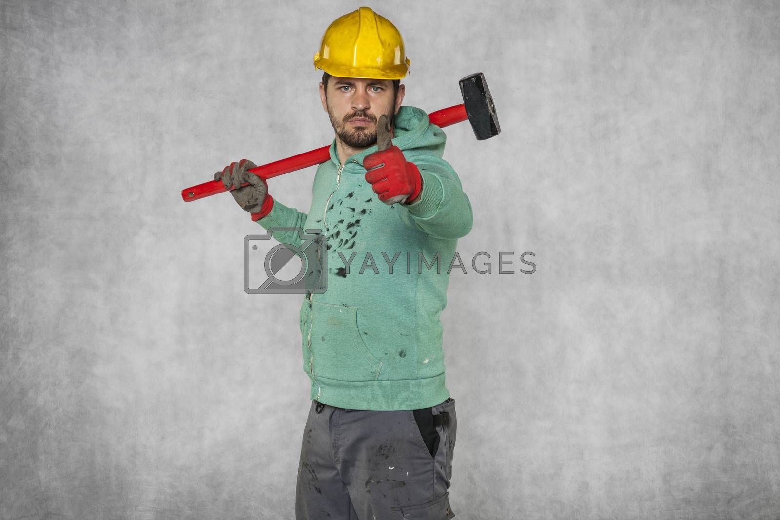 happy worker with a hammer on his shoulder