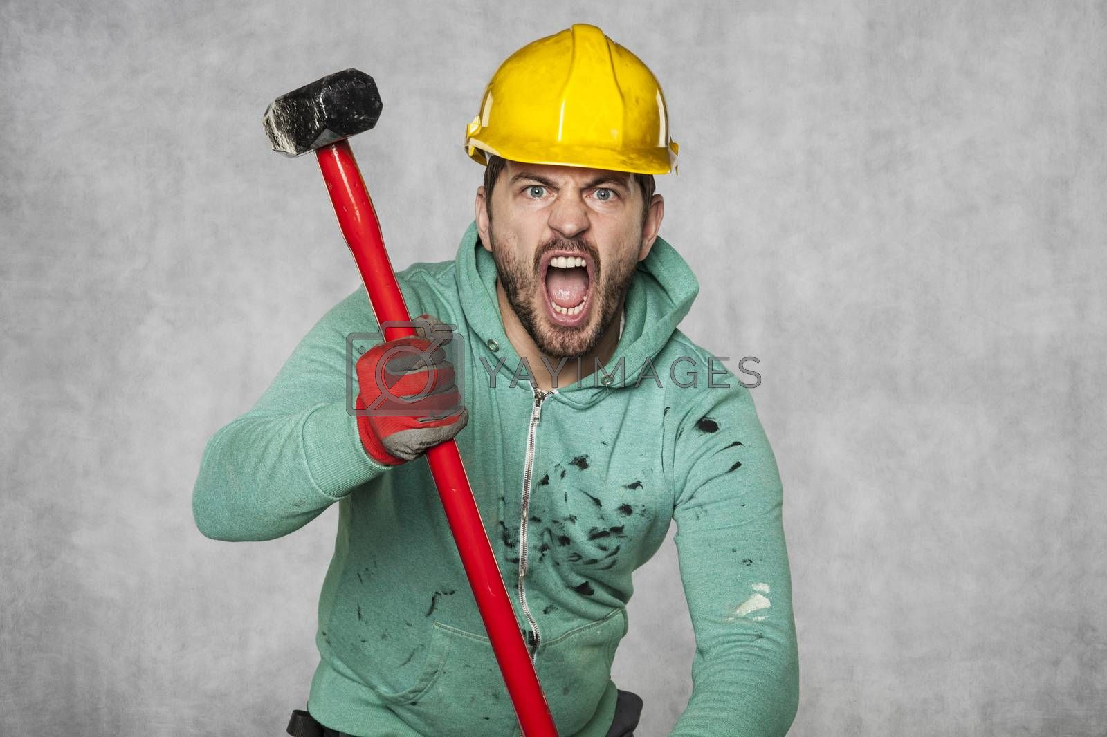 A worker with a big hammer screams like a possessed man