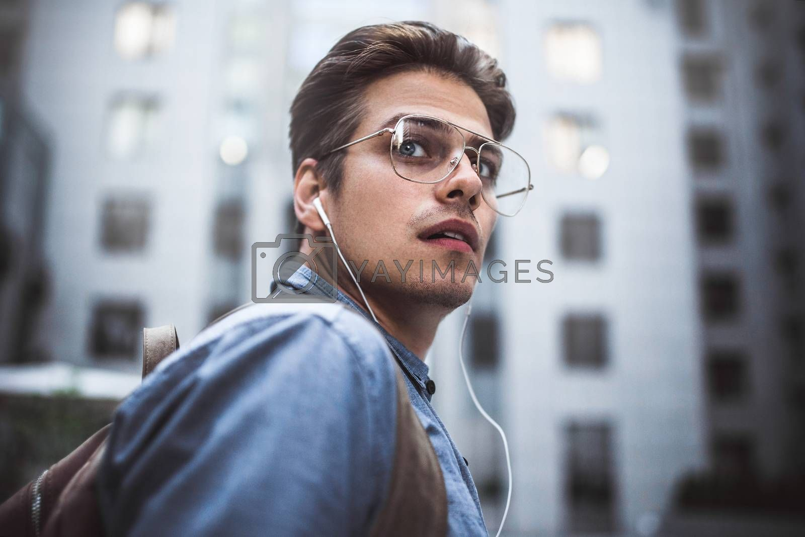 Portrait of handsome successful businessman walking on the street and thinking about startup project.