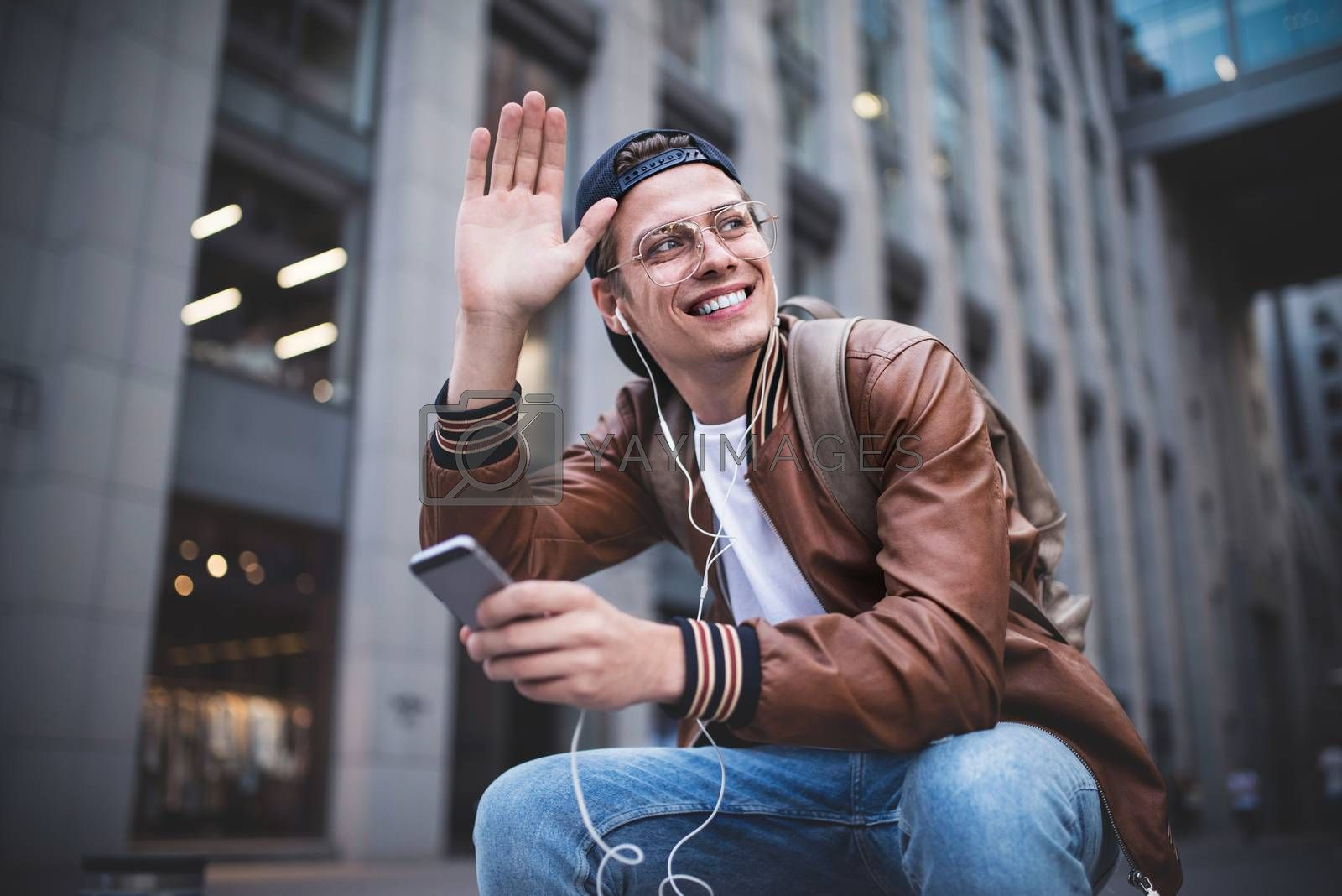 Man Sitting Listening Music Earphones Concept. Cheerful young guy listening the music.