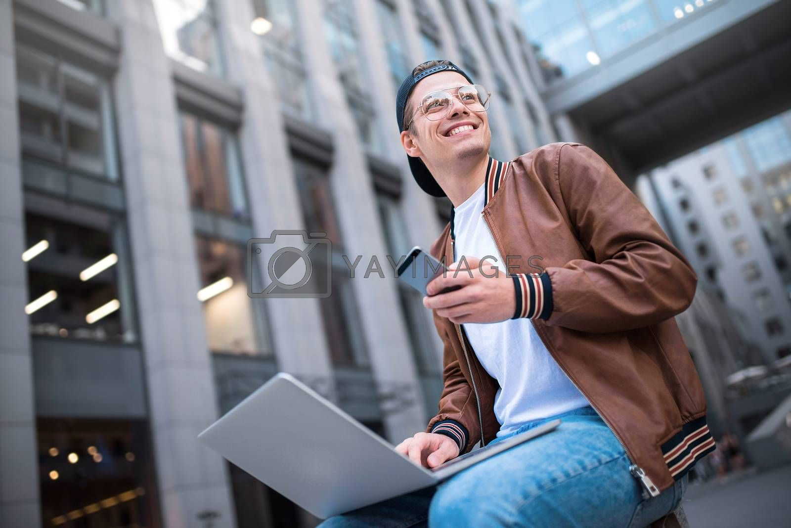 Royalty free image of Smart attitude. Positive handsome man using a laptop and sitting in the street while surfing the internet have a web conference. Web chat online conference. by Nickstock