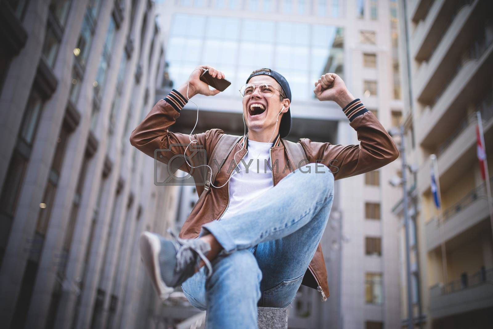 Royalty free image of Happy man listening to music with headphones from a smartphone on the street. by Nickstock