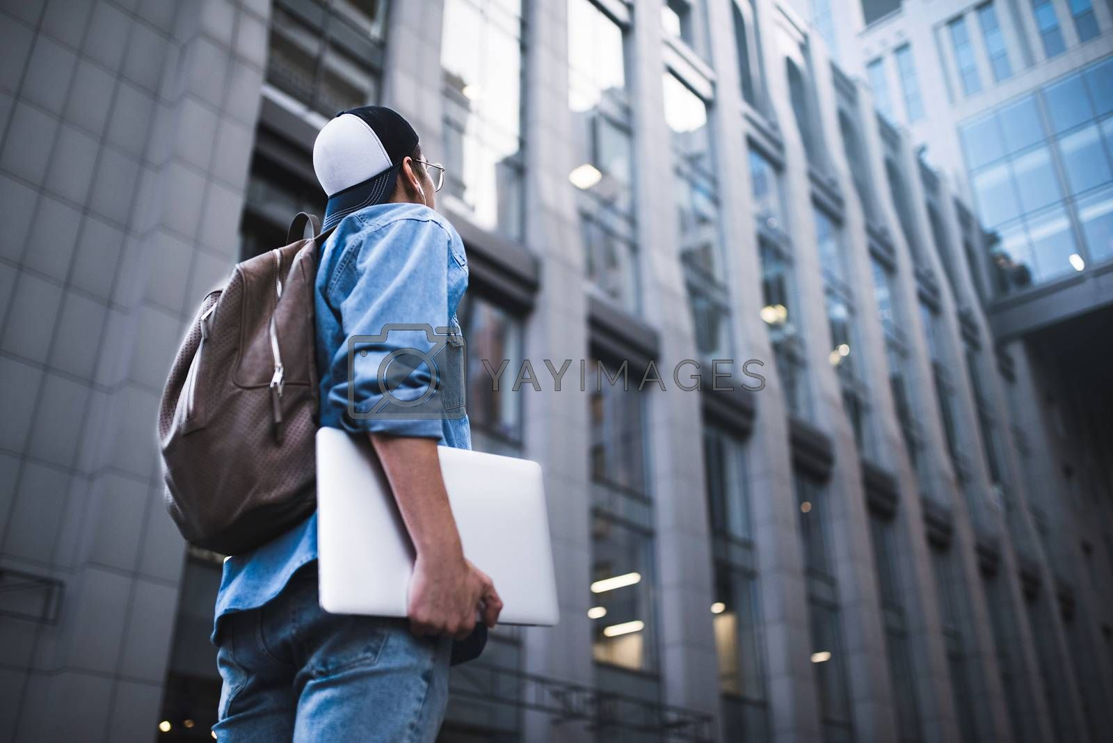 Outdoor portrait of handsome young male student with backpack standing at building background on the street while waiting his colleagues. Businessman wearing casual white shirt and spectacles. People