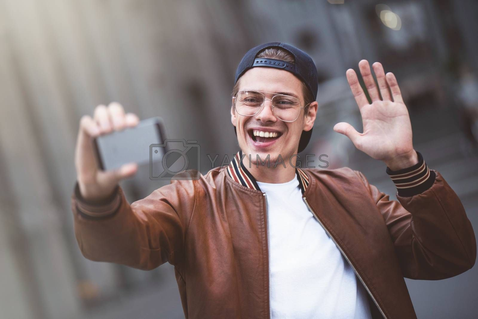 Selfie mania Excited young guy is making selfie on a camera. He is wearing casual trendy wear and snap back