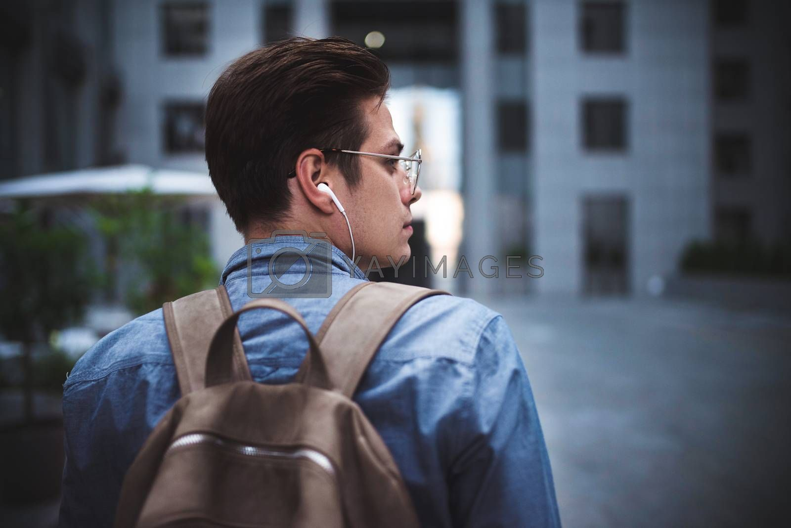 Royalty free image of Portrait of cheerful young handsome well dressed man with headphones thinking about new project. by Nickstock