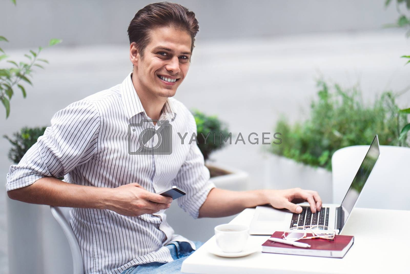 Smart attitude. Positive handsome man using a laptop and sitting in the cafe while surfing the internet.