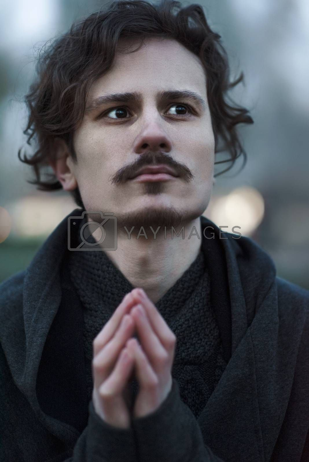 Handsome young curly man feels alarm about future and small tenseness. Concept of prayer and desire for plans to be succeeded