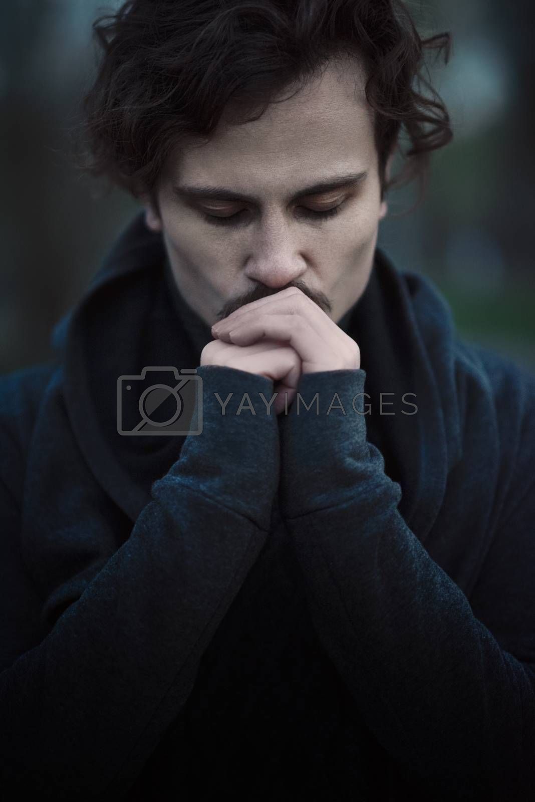 Royalty free image of Handsome young curly man feels faith and hope. kisses his own hands by Nickstock
