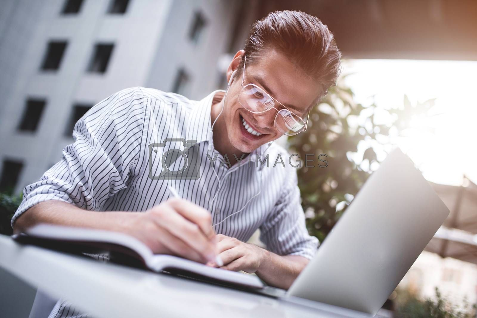 Royalty free image of Smart attitude. Positive handsome man using a laptop and sitting in the cafe while surfing the internet. Young blogger or journalist or designer working outdoor. by Nickstock