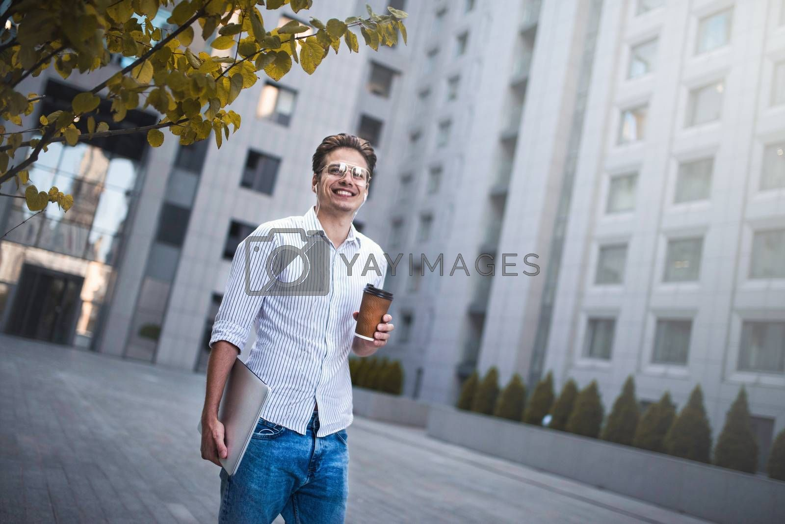 Royalty free image of Portrait of handsome successful businessman walking on the street and thinking about startup project. by Nickstock