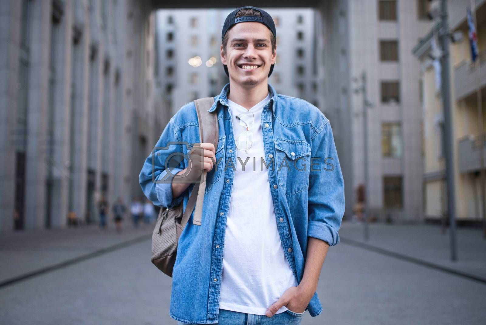 Royalty free image of Cheerful young man with backpack enjoying walk the city by Nickstock