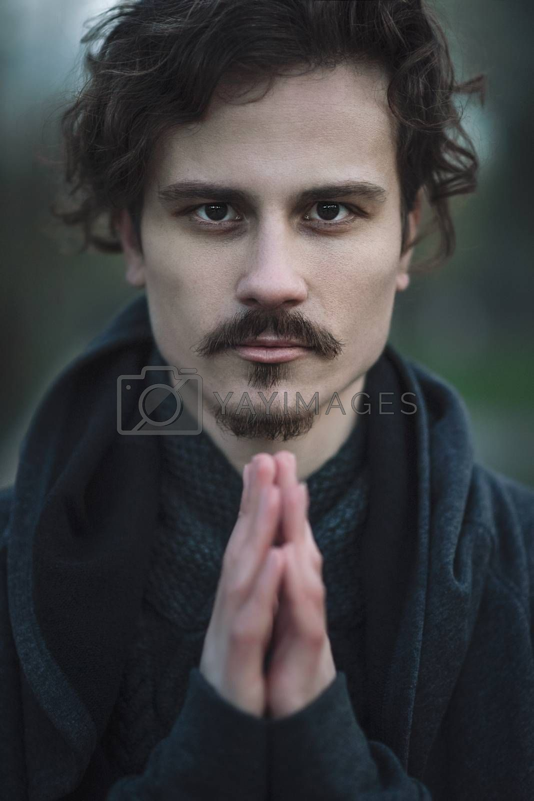 Handsome young curly man bears deep religious feelings. Faith. Hope. Acumen.