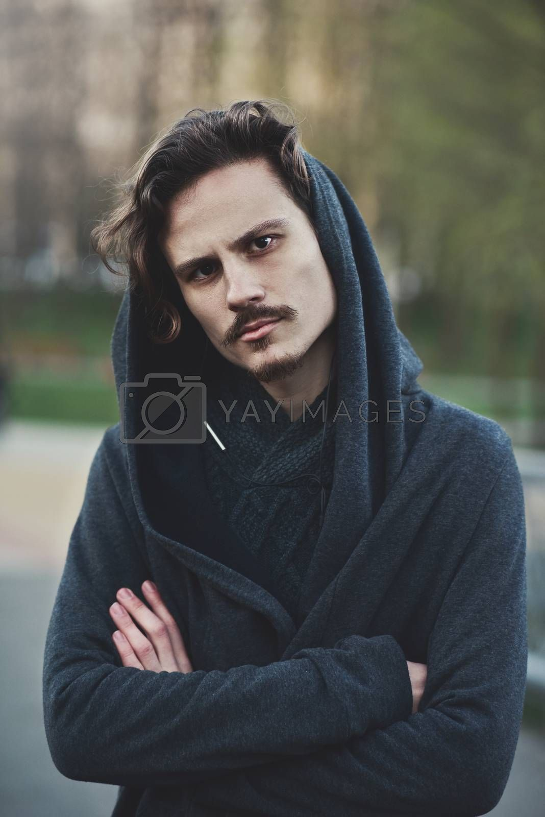 Royalty free image of Handsome young hooded man looks on something with suspicion by Nickstock