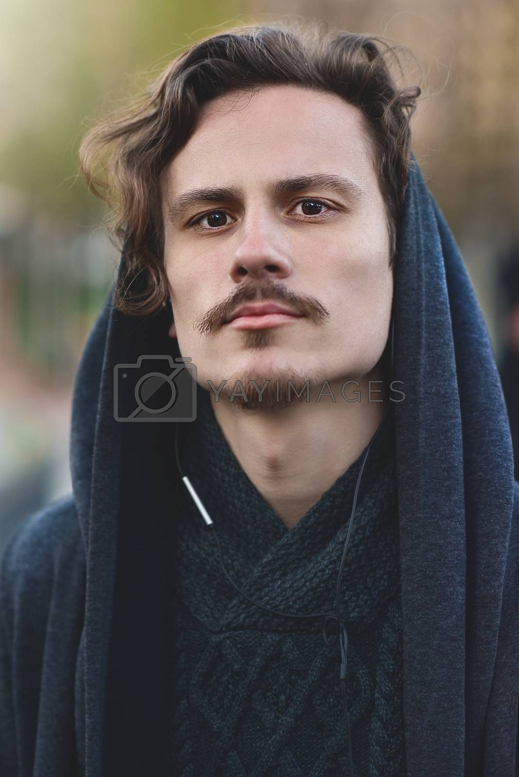 Royalty free image of Handsome young curly hooded man ponders something, looking into the camera. reeady to fight by Nickstock