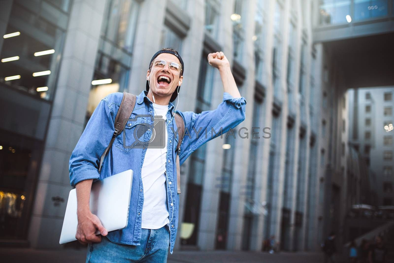 Royalty free image of Say hello. Happy man meeting someone. Happy man listening to music with headphones from a smartphone on the street. by Nickstock