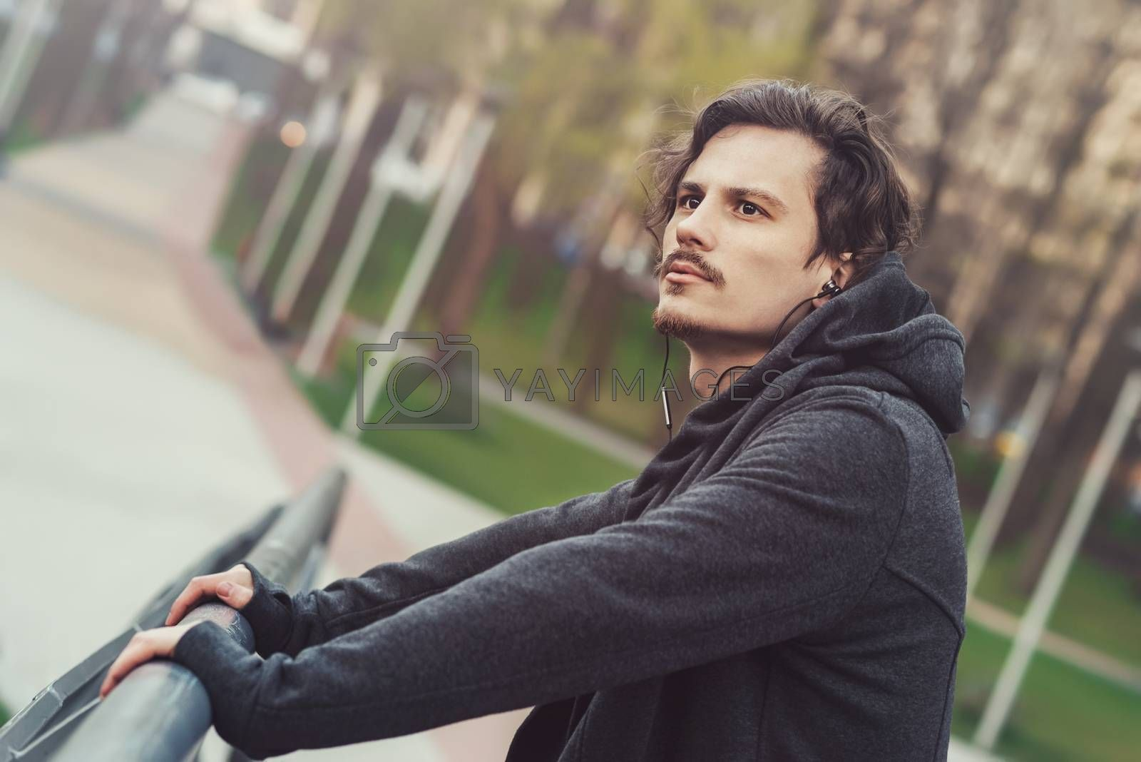 Portrait of a Young man listening to music, standing on the bridge and enjoying the beautiful view.
