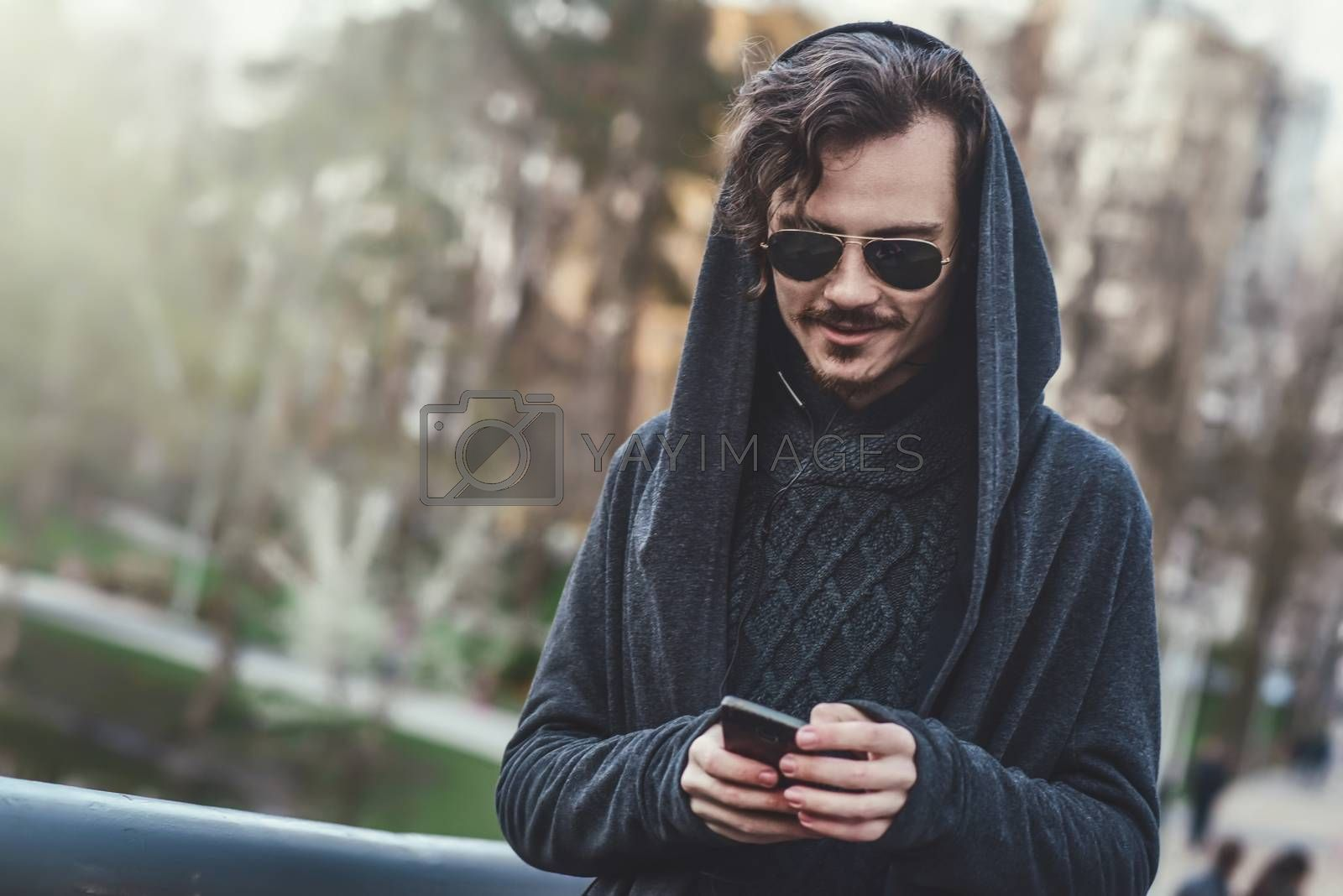 hooded stylish man in sunglasses walks In the park and texting message by Nickstock