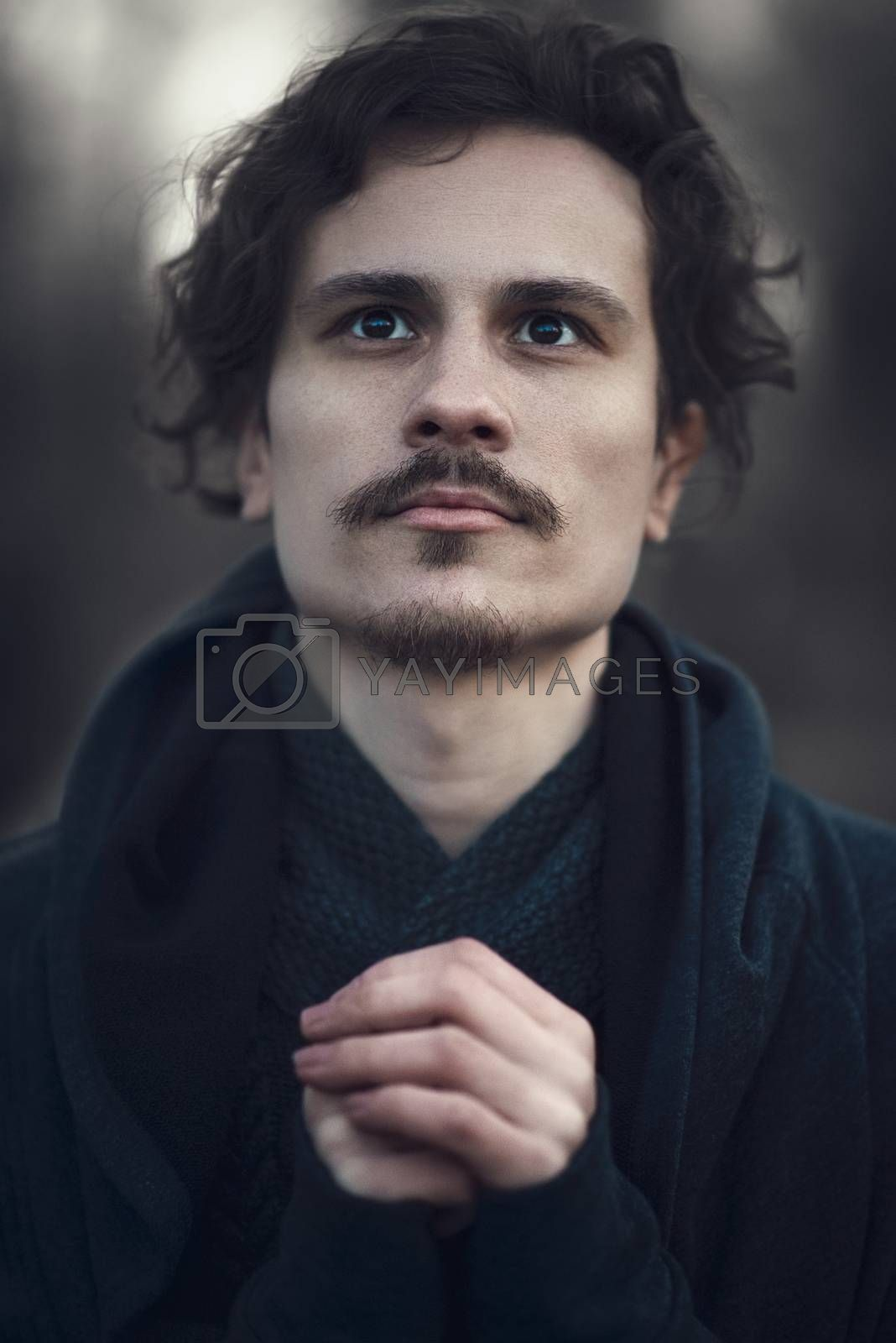 Handsome young curly man hopes for better future. Invocation to the God. Religion concept
