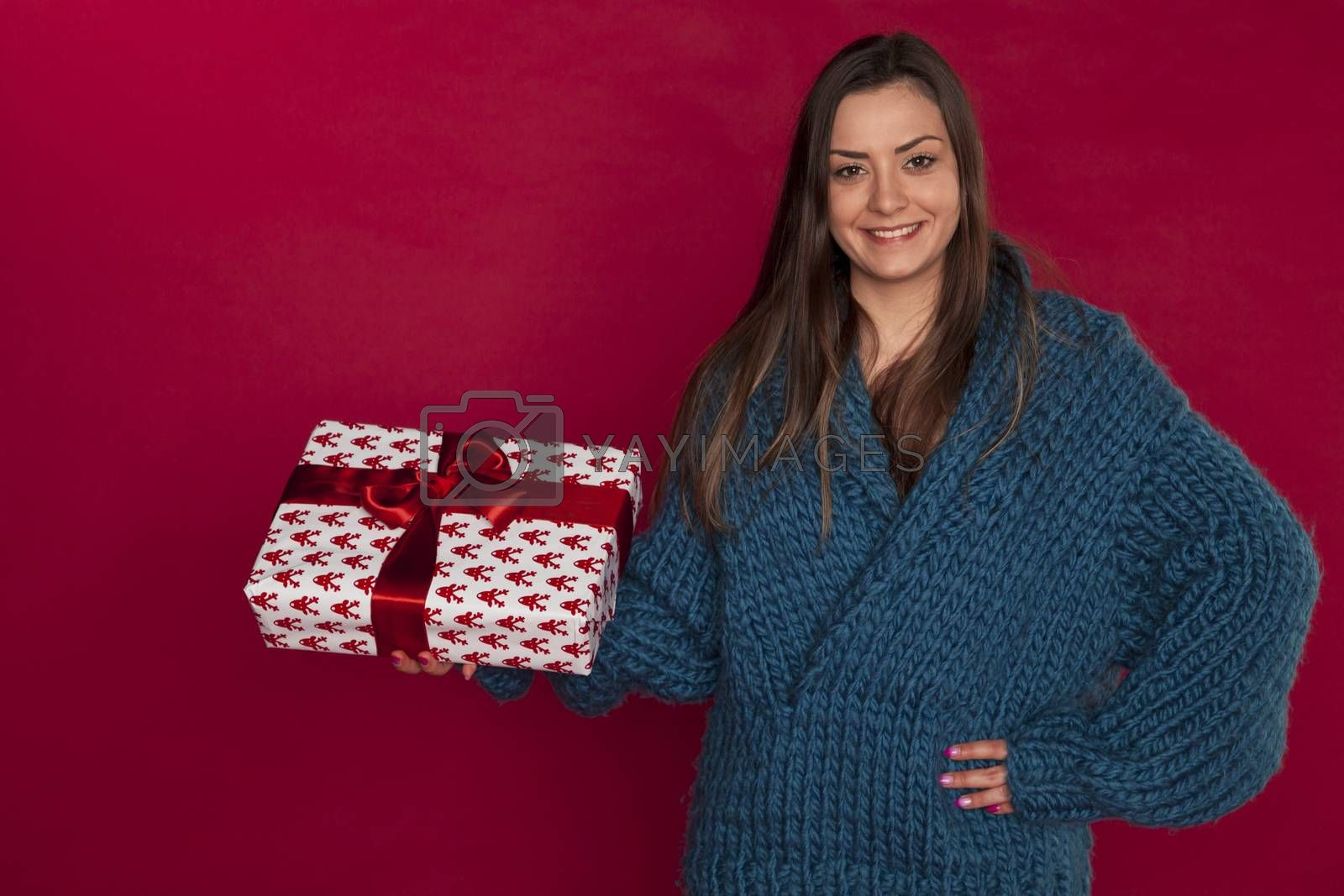 young girl in blue sweater holding a christmas gift